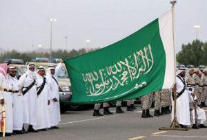 Members of Saudi al-Mujahdeen forces hold up the Saudi Arabia flag in Arafat