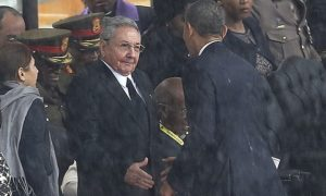 Barack Obama shakes hands with Cuba's President Raúl Castro at a memorial service for Nelson Mandela