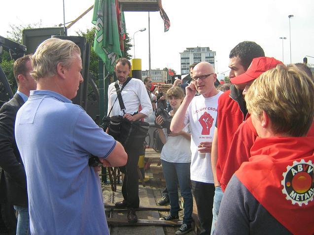 Een deurwaarder staat tegenover arbeiders bij Crown Cork.